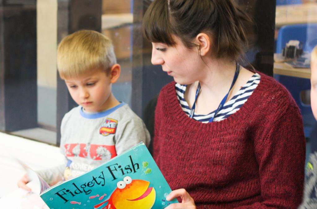 Nursery teacher reading to pupil