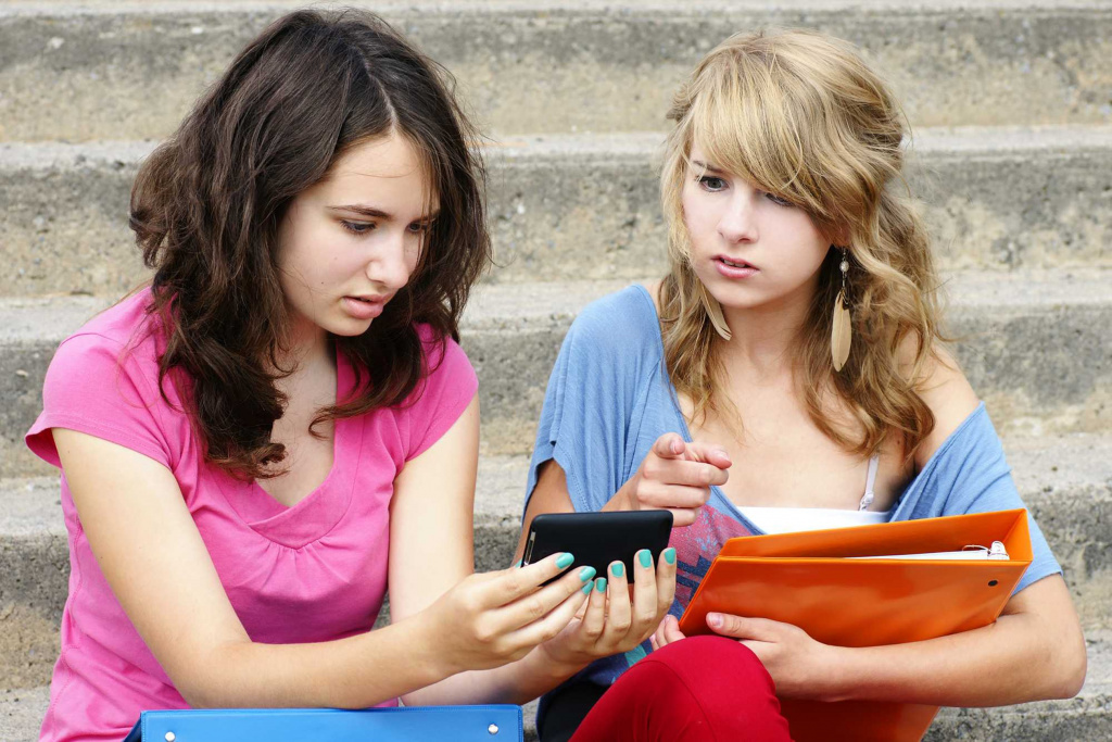 Students looking at a mobile phone with very serious faces