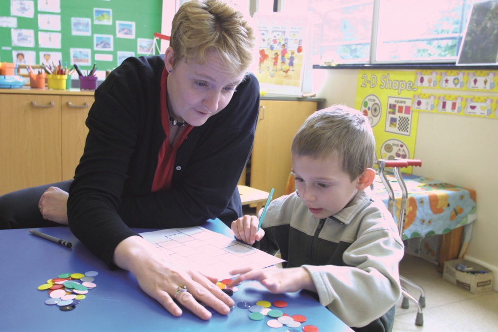 Teacher helping SEN primary pupil with counters