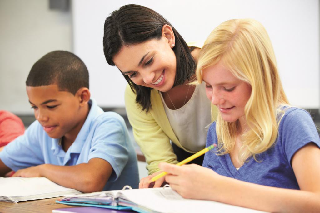 Teacher helping secondary pupils work at desk