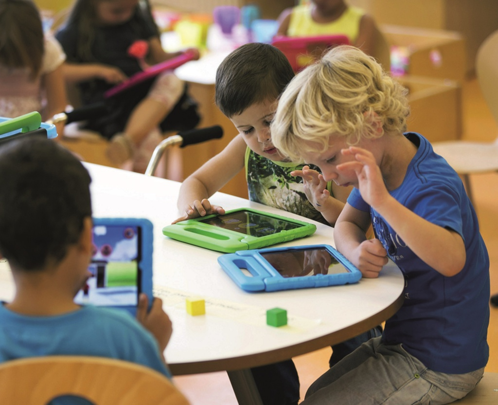 nursery age children using tablets at desk
