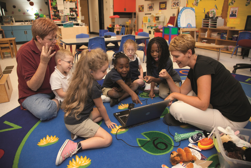 children on play mat looking at laptop with teachers