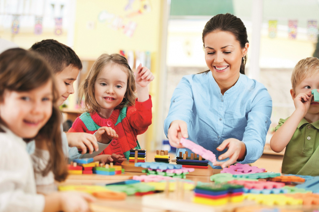 Nursery teacher playing at desk with pupils