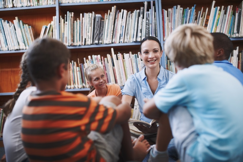 Teacher sitting with primary students in library