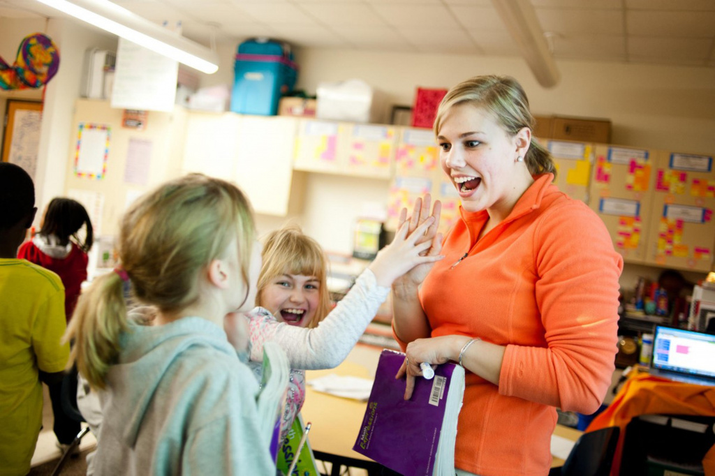Teacher high-fiving primary pupil
