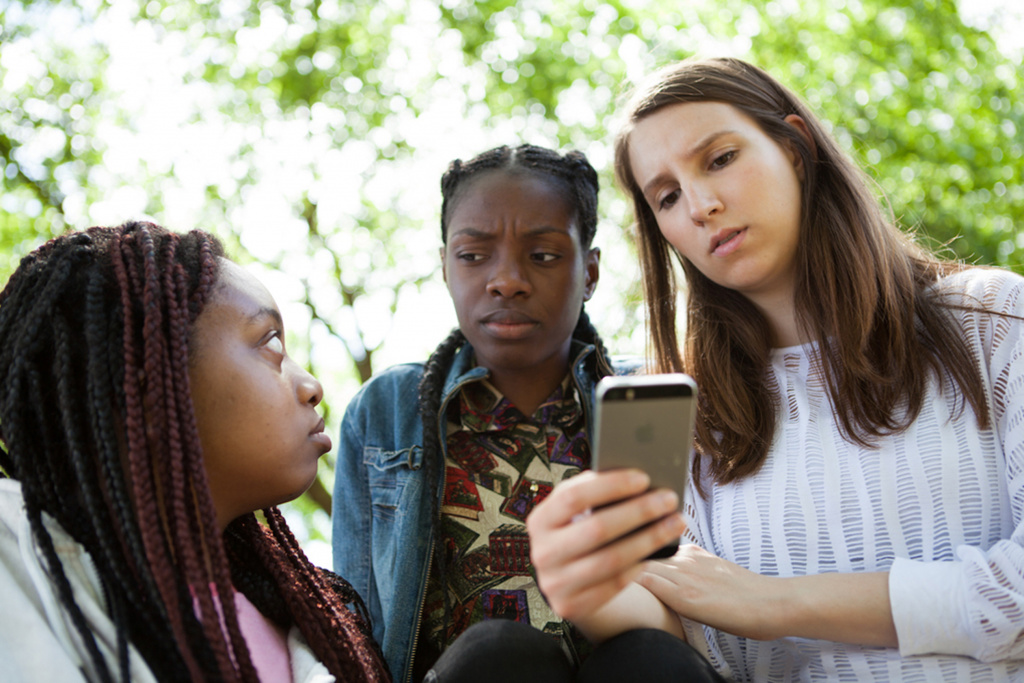 Young people looking at phone in contempt