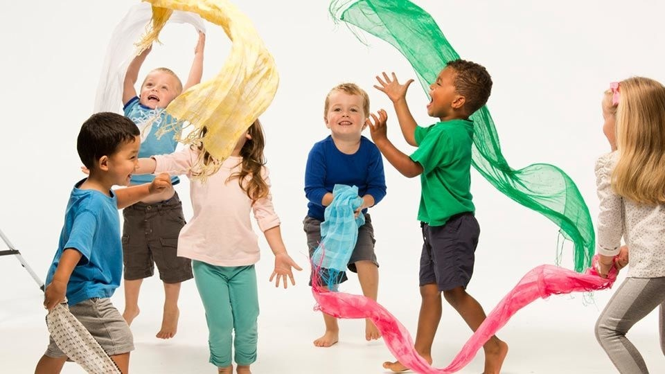 Pre-school children dancing with colourful scarfs