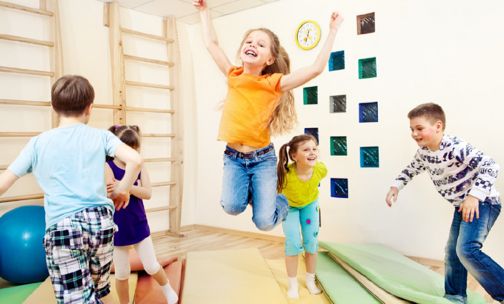 young children in gym room with girl at centre jumping high