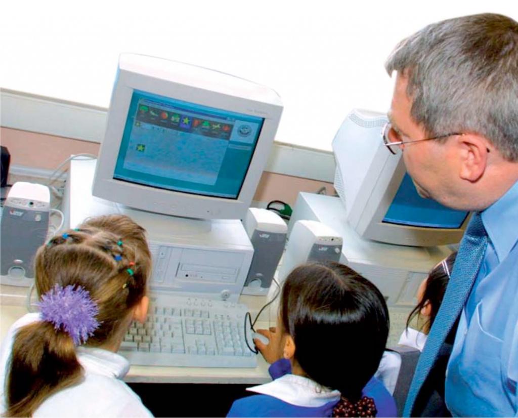 Teacher teaching pupils how to use a computer