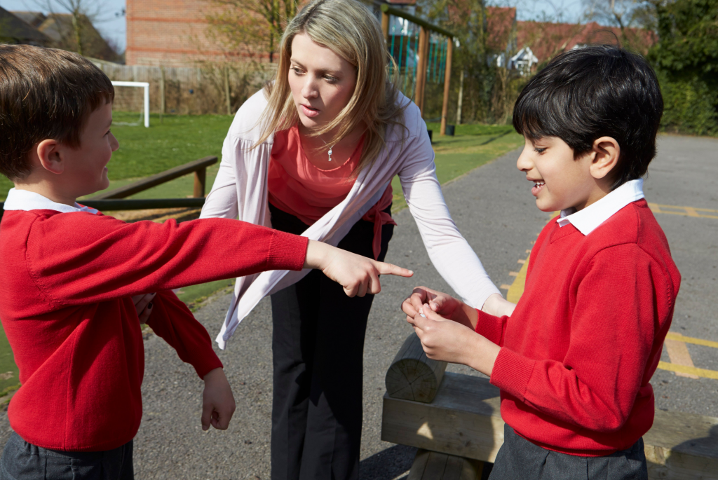 Teacher tries to resolve conflict between two young pupils
