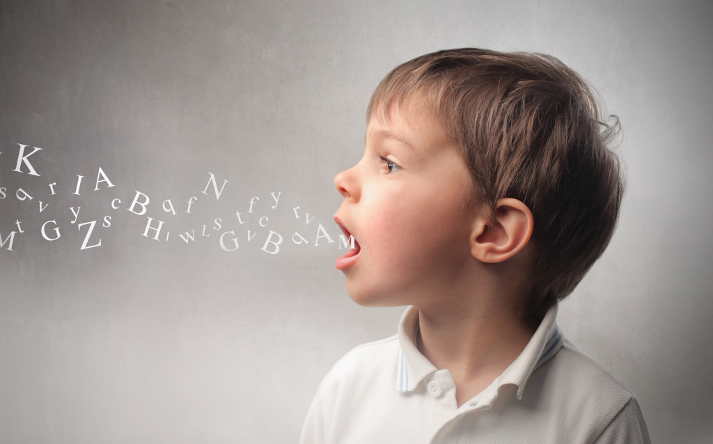 Young boy with letters floating from his open mouth