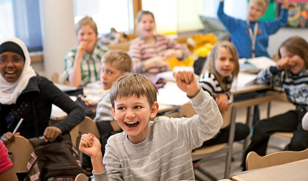 Boy cheering in class with hands in air