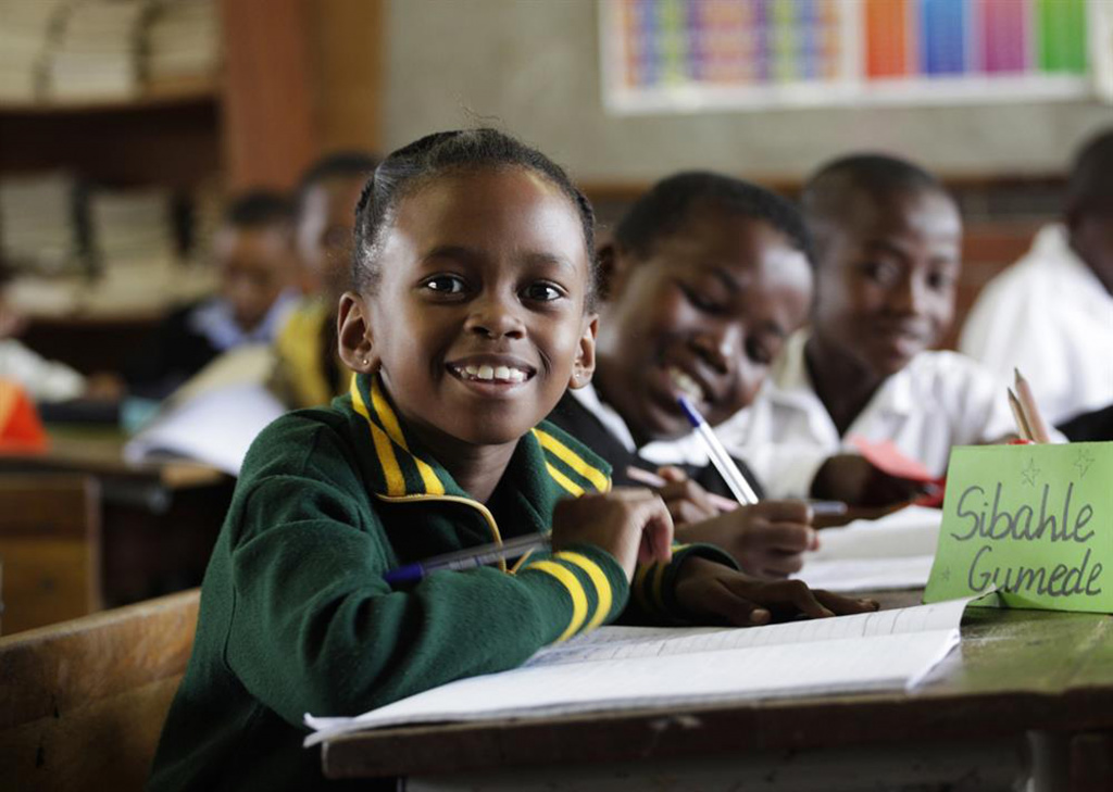 young girl at desk smiling