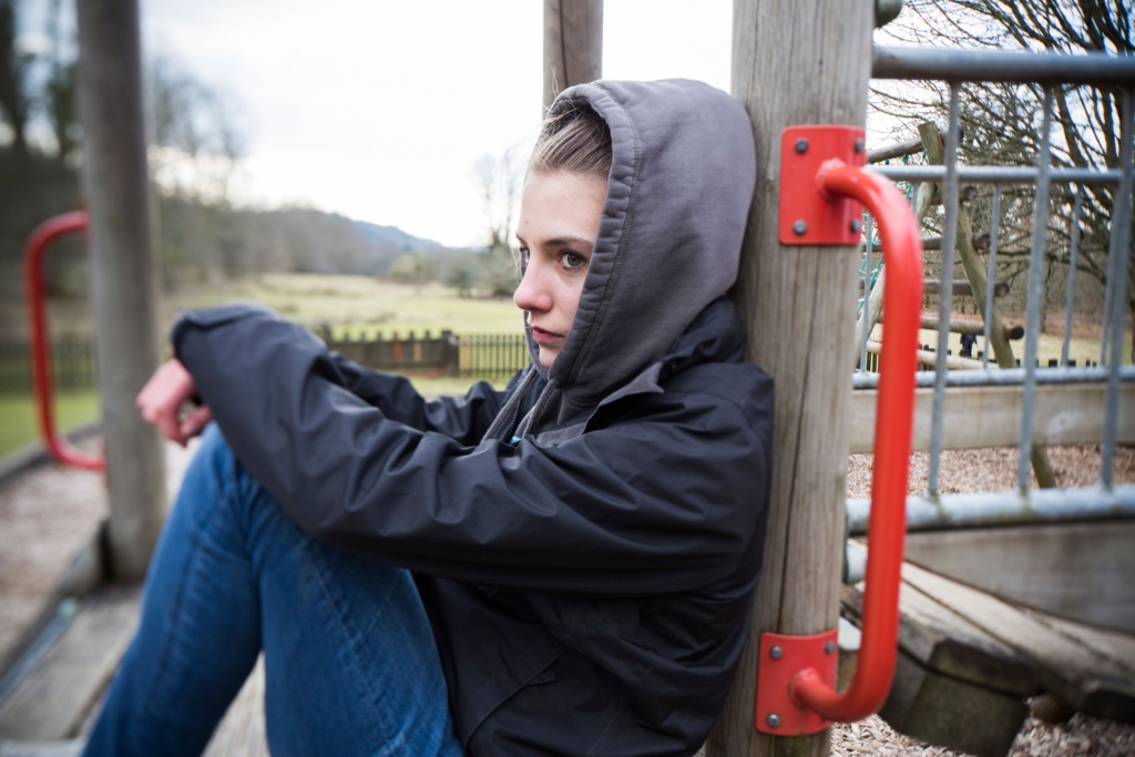 A teenage girl sitting in a children's play area looking despondent and depressed