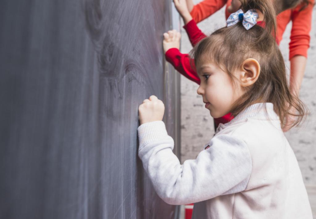 Child writing on black board