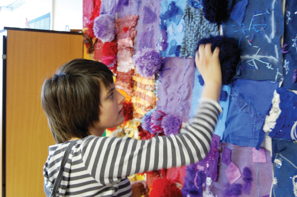 Autistic pupil playing with sensory wall