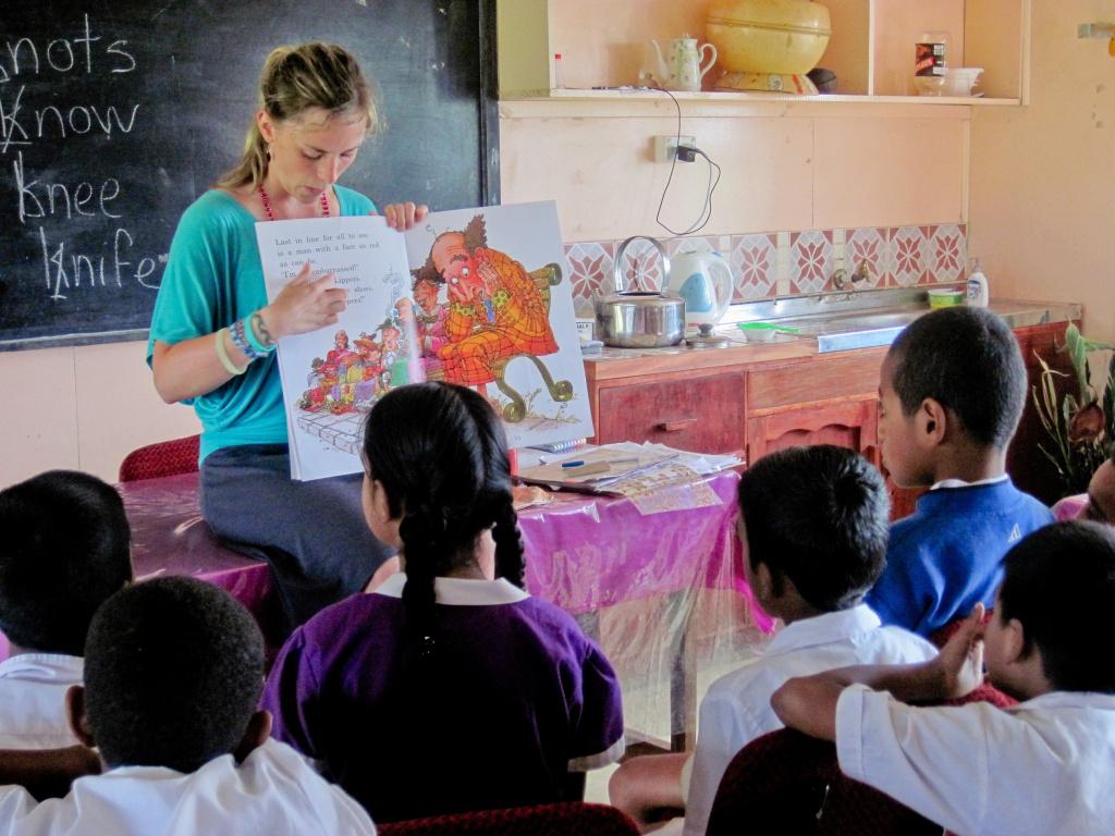 Teacher showing cartoon cat to young pupils