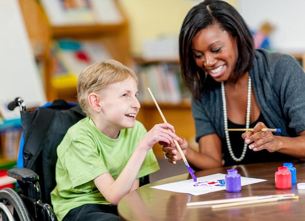 Boy in wheelchair enjoying painting with teacher