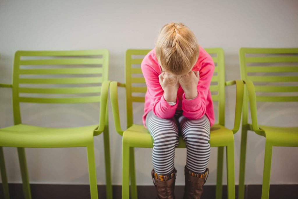 Girl sitting in green chair crouched with face in hands