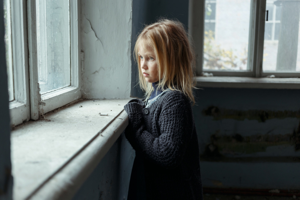 Poor young girl looking out of dirty window