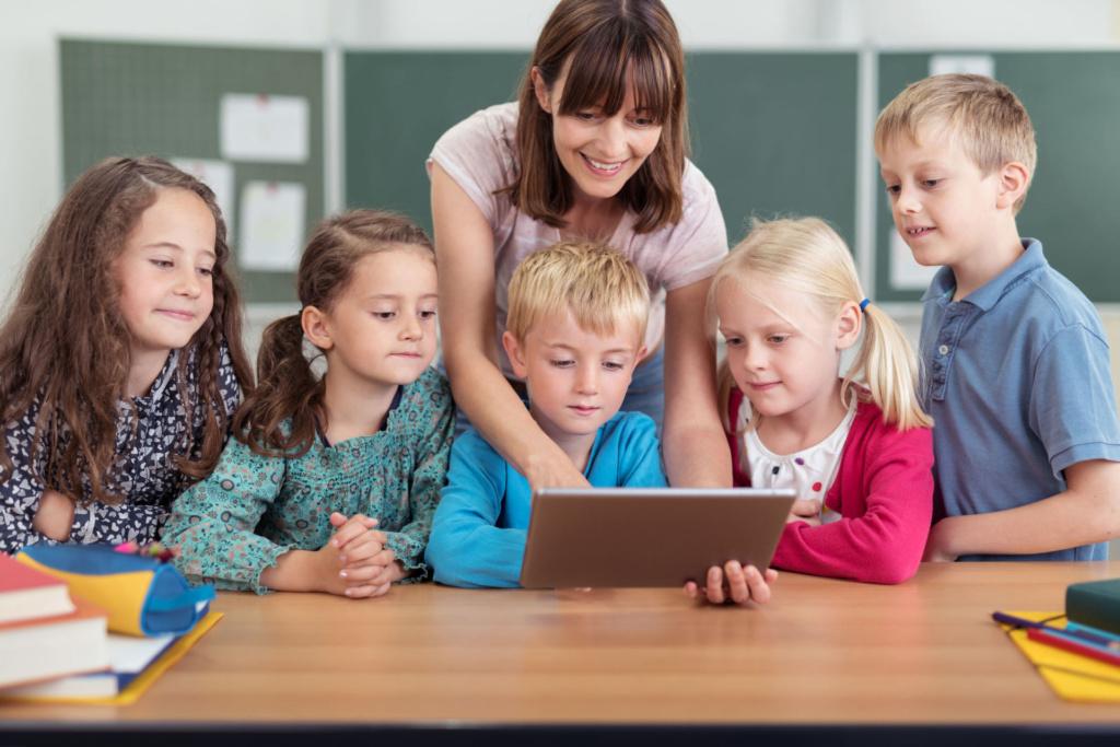 teacher and children gathered around laptop