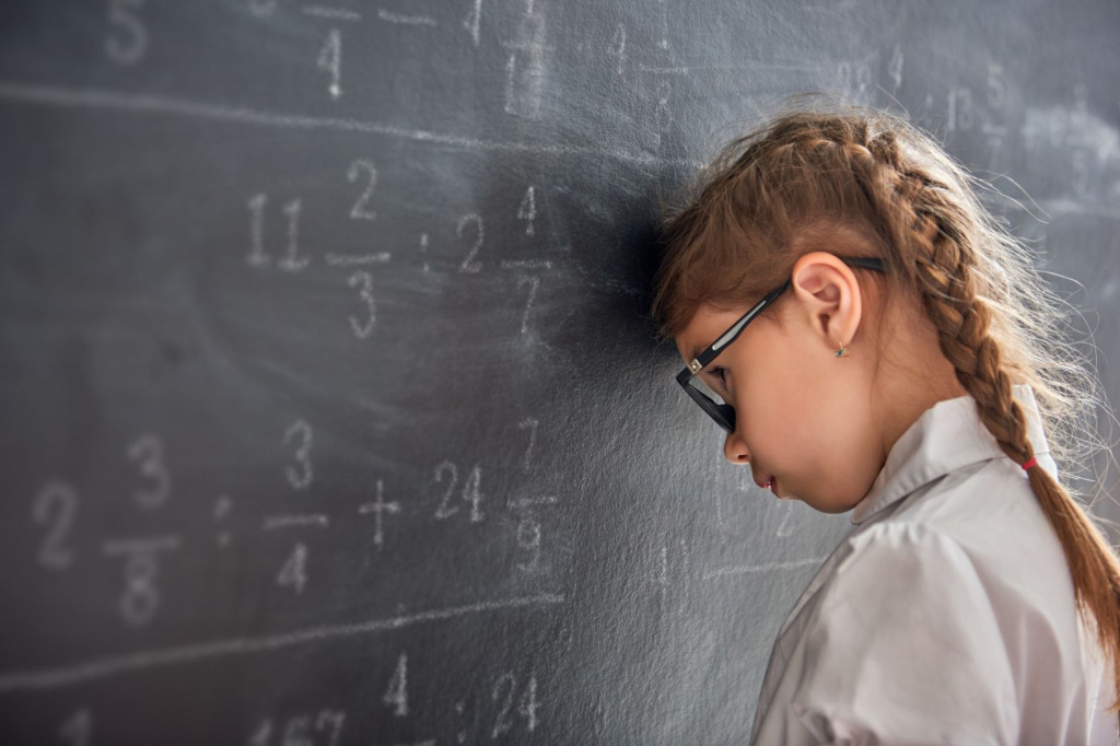 Young pupil struggling with calculations on black board