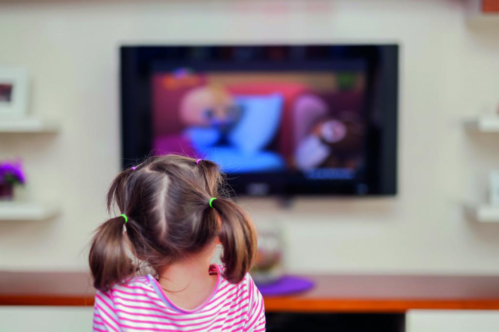 Cute little girl watching cartoons