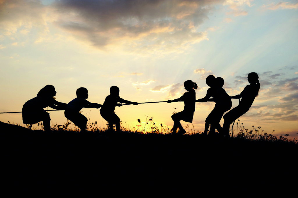 Children playing tug of war in a field.
