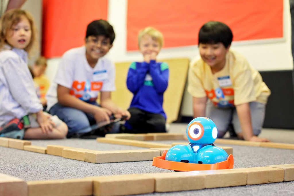 Young pupils playing with robot