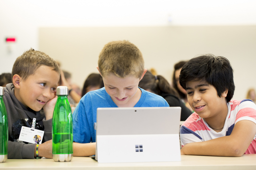 Young pupils using laptop