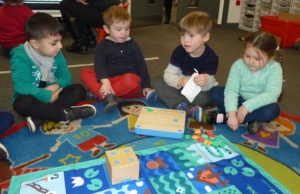 children sitting round a mat with a small wooden cube robot