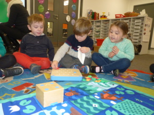 Children sitting round mat and looking at small wooden cube robot