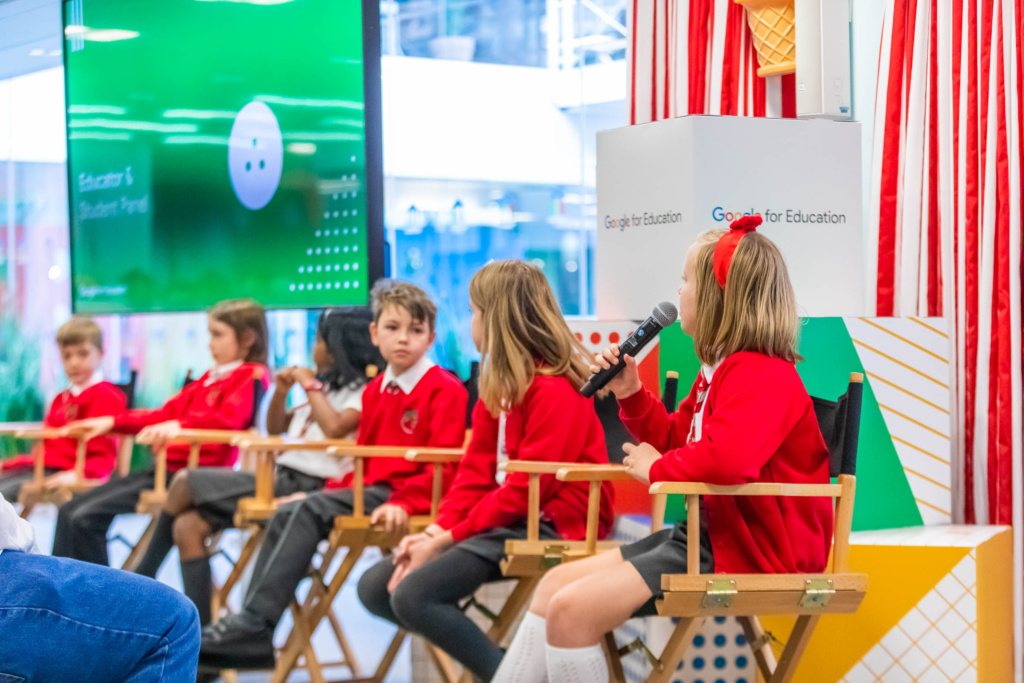 Six primary children in school uniform presenting at a Google event