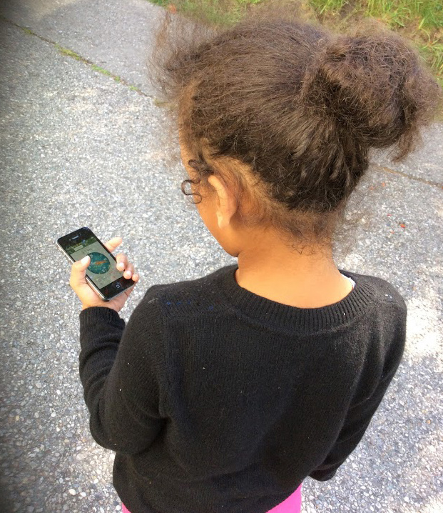 Back view of a girl holding a mobile phone