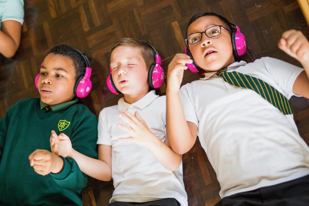 Three children with pink headphones