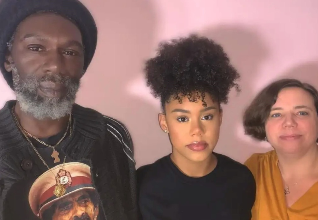 A girl with Afro hair standing between Rastafarian father and white mother