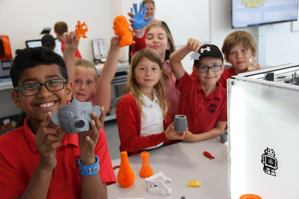Six primary aged children holding up masks they have made on 3D printers