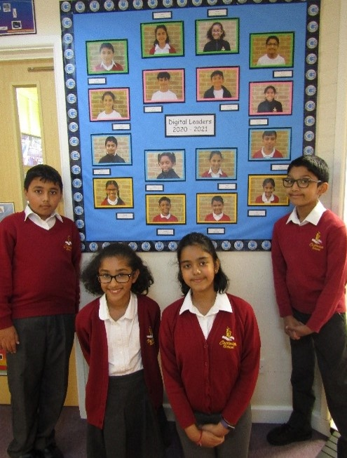 Four children in school uniform standing by a Digital Leaders Display board rom