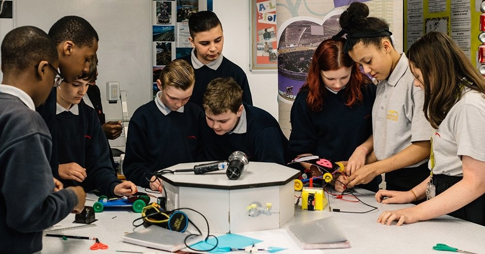 Nine students looking at a range of sensors and robotic toys