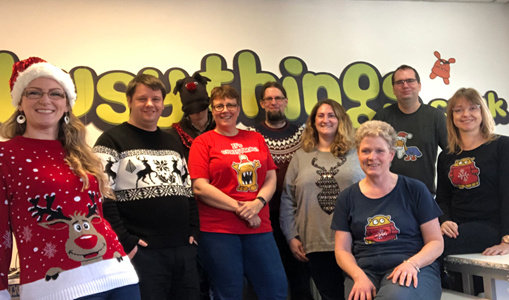 Woman with Santa hat and 8 employees in Christmas jumpers
