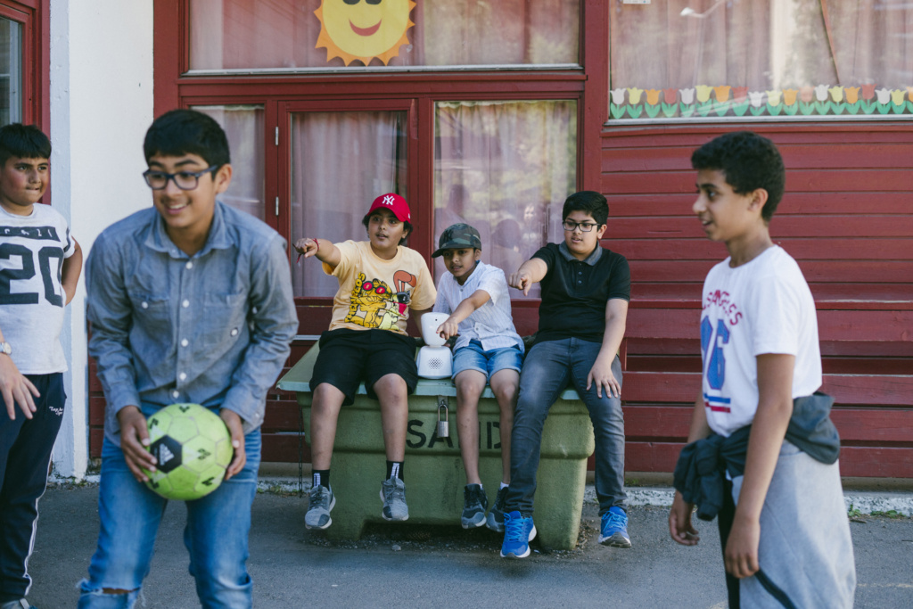 Three boys playing ball in the playground with three other boys and an AV1 robot on a bench watching