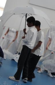 Two boys in school uniform holding a white umbrella