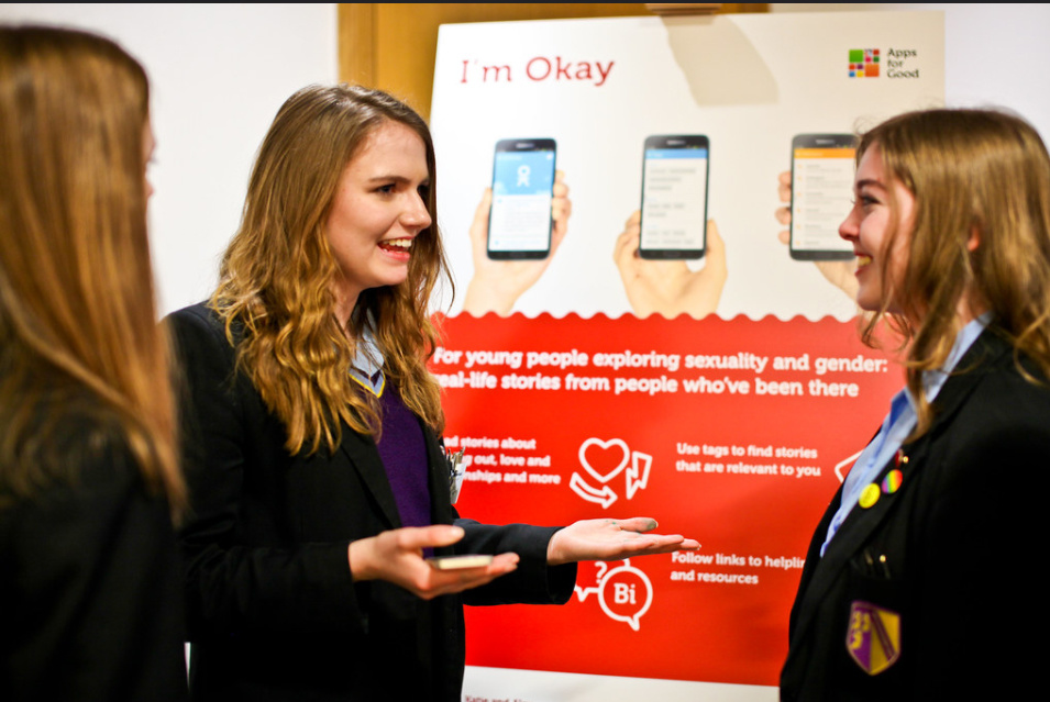 three girls smiling with pop up poster for their app