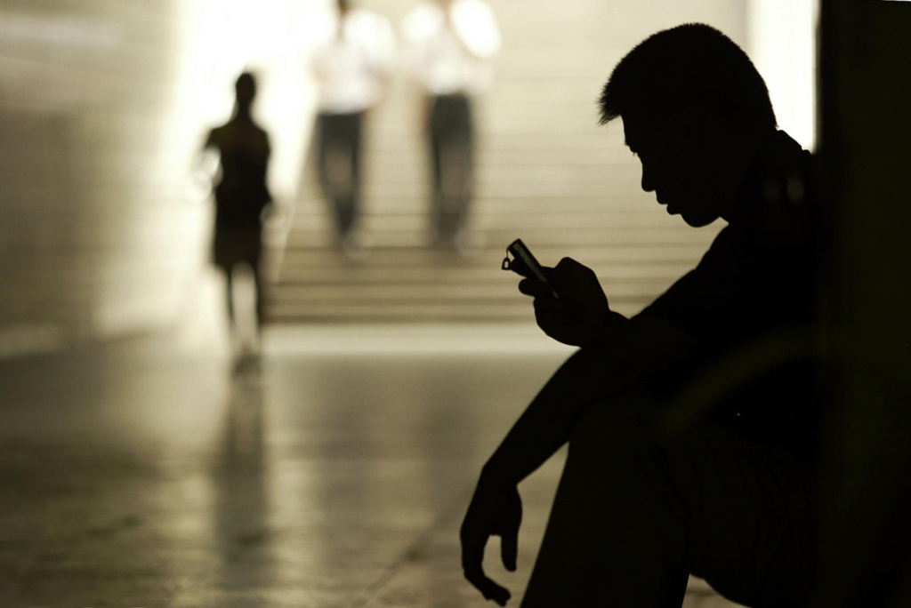 Silhouette of young man sitting on floor by stairs looking at his phone