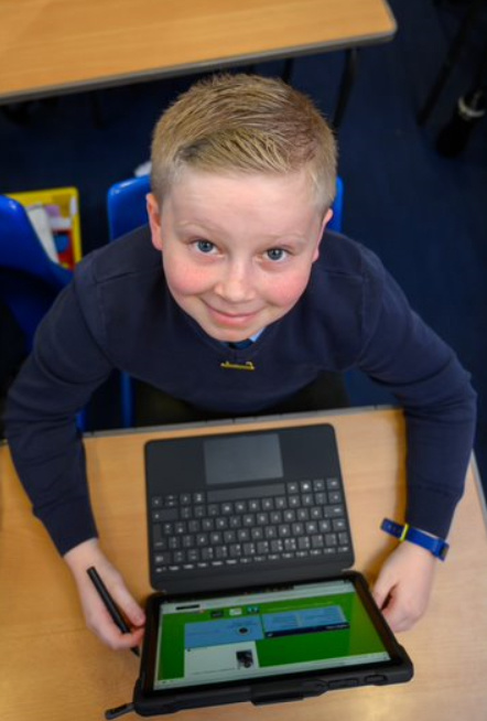 Cheeky smaile of a child enjoying his laptop