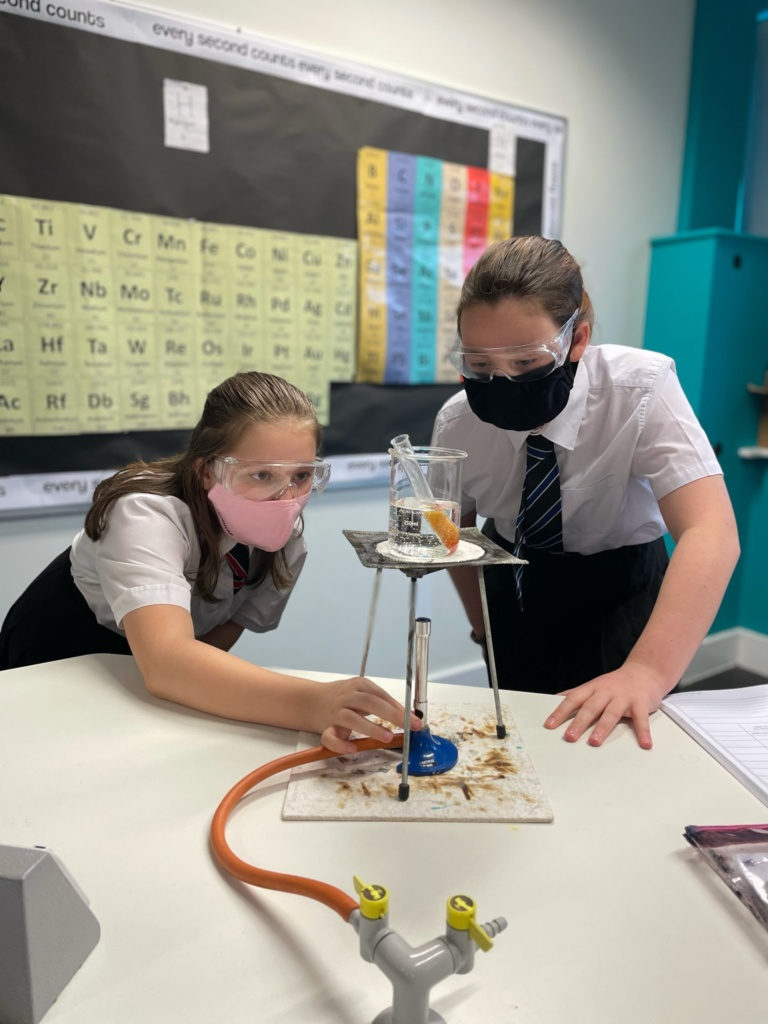 two girls with bunsen burner and flask doing an experiment