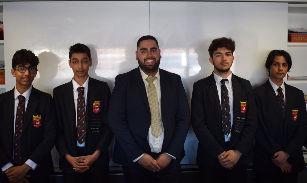 four male students in school uniform with a teacher in suitand tie standing in the central position