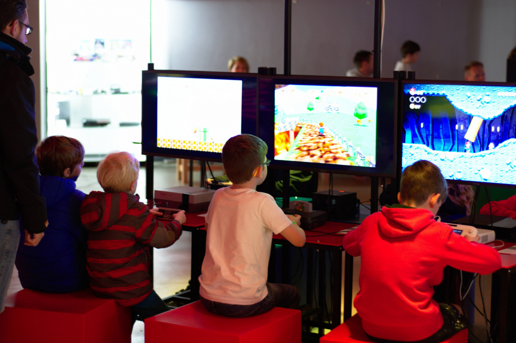 4 young children at a museum looking at screens