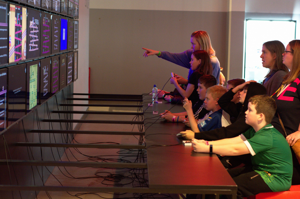 6 children and 3 aduslt looking at a bank of screens fetrugin different games